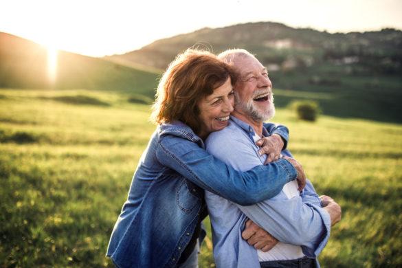 Ein älteres Paar lachend sich umarmend in sonniger, grüner, hügeliger Landschaft.