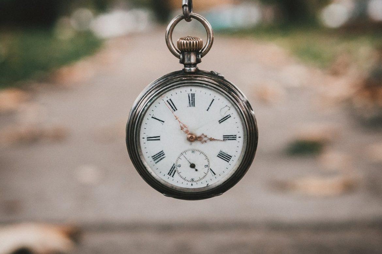 EIne Taschenuhr hängt an einer Kette vor einem Weg.