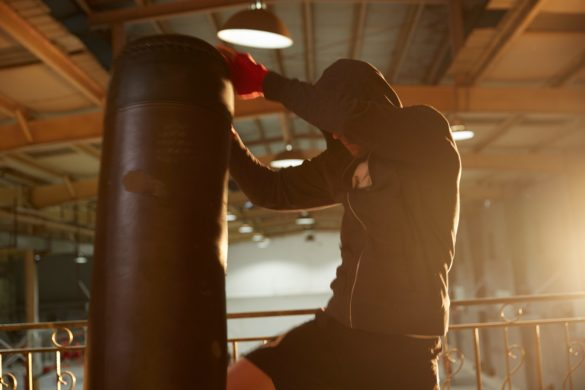 Ein Mann trainiert mit einem Boxsack