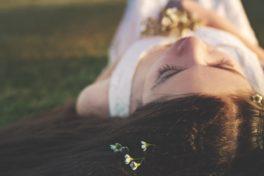 Junge Frau mit dunklen Haaren liegt mit geschlossenen AUgen schlafend auf einer Wiese mit Blumen in den Haaren und in der Hand.
