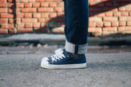 Eine Person trägt Sneakers und Jeans und steht aufrecht auf einem Betonboden