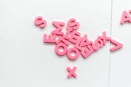 Pinke, rosane plastik Buchstaben auf weissem Tisch.