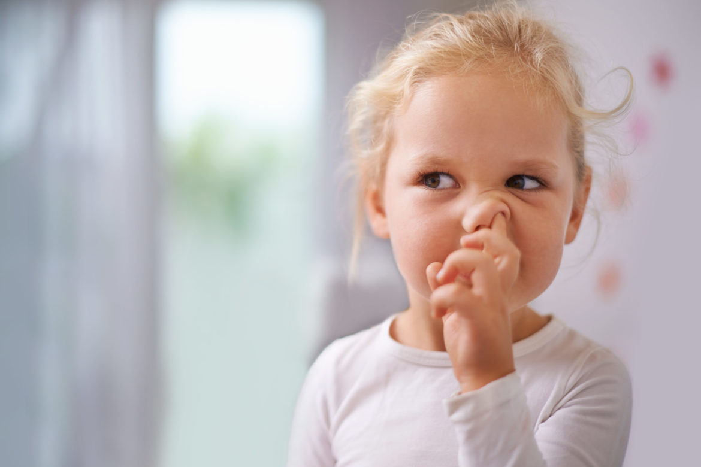 Ein blondes lockiges Mädchen popelt in der Nase.