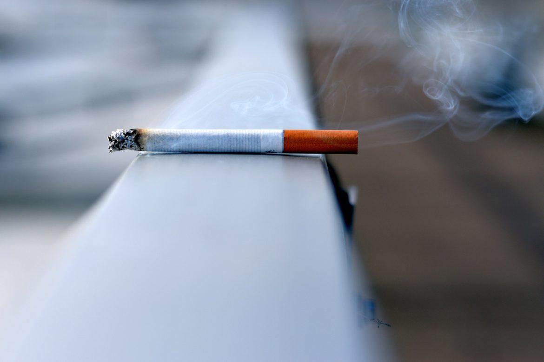 Ein brennende Zigarette auf einem Geländer.
