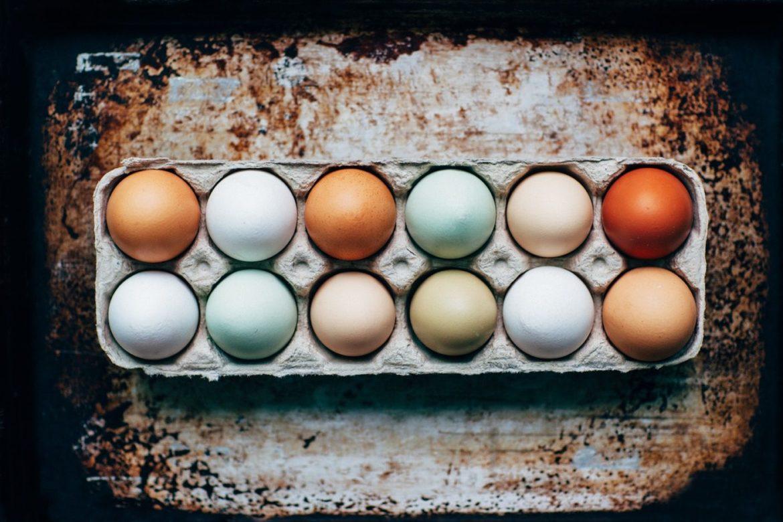 Ein Eierkarton mit zwölf braunen, weissen, blauen Eiern.