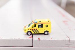 Ein kleiner Spielzeug Krankenwagen auf weissen Holzdielen.