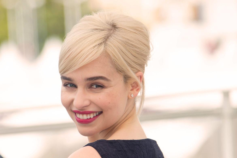 Game of Thrones Schauspielerin Emilia Clarke lächelt mit blonden Haaren und roten Lippen in die Kamera.