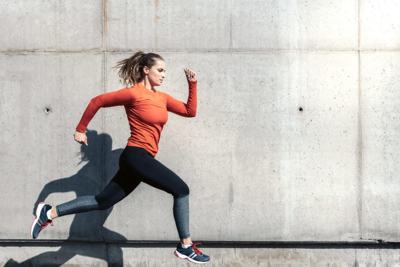 Junge Frau in Sportkleider im Laufen vor Betonwand.