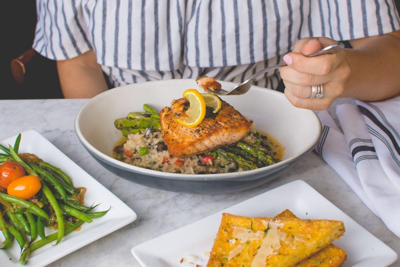 Eine Frau sitzt an einem Tisch und isst Lachs mit Gemüse, Reis, Toast, Bohnen.