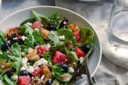 Zwei Teller mit Salat, Dressing auf einem Tisch.