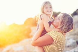 Mutter spielt mit ihrer Tochter in der Sonne