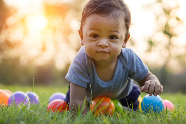 Asiatisches Baby mit dunklen haaren krabbelt auf Gras zwischen bunten Bällen.