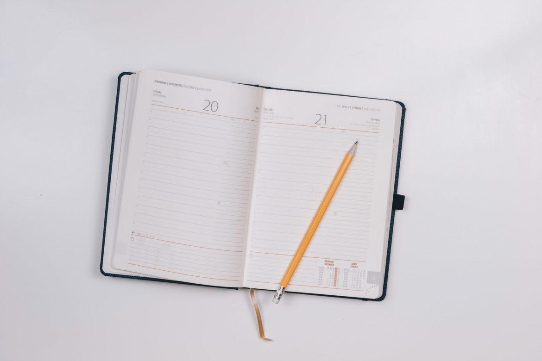 Ein Terminplaner mit gelbem Bleistift auf weissem Tisch.