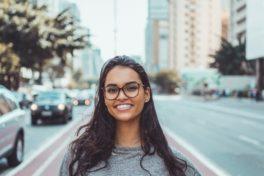 Eine Frau mit Brille, die lacht.