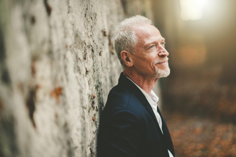 Älterer Mann lehnt an Steinmauer - Brustkrebs beim Mann