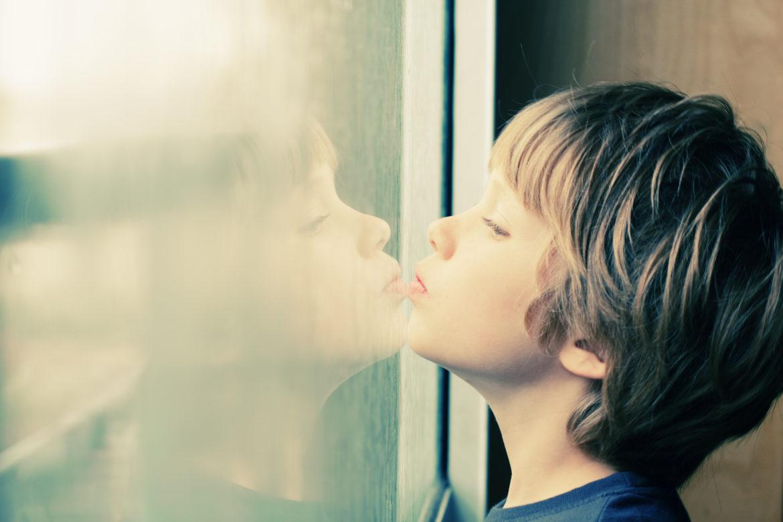 Junge guckt durch Fenster-Sehfehler Kinder