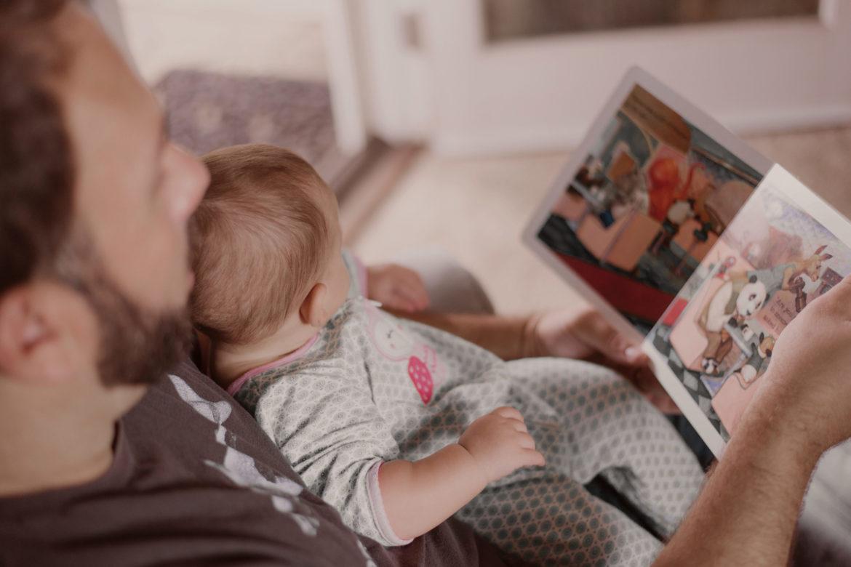Kleinkind im Arm von Vater mit Buch - Vorlesen