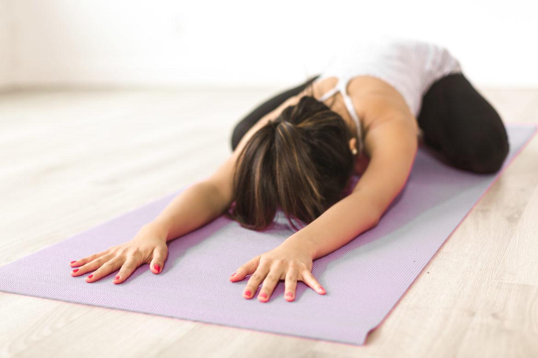Frau in Yogapose Kindshaltung, Child's Pose