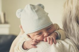 Ein Baby liegt an der Schulter seiner Mutter