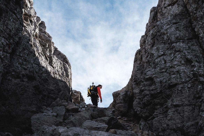 Wanderer zwischen zwei Felswänden - Sicher unterwegs in den Bergen