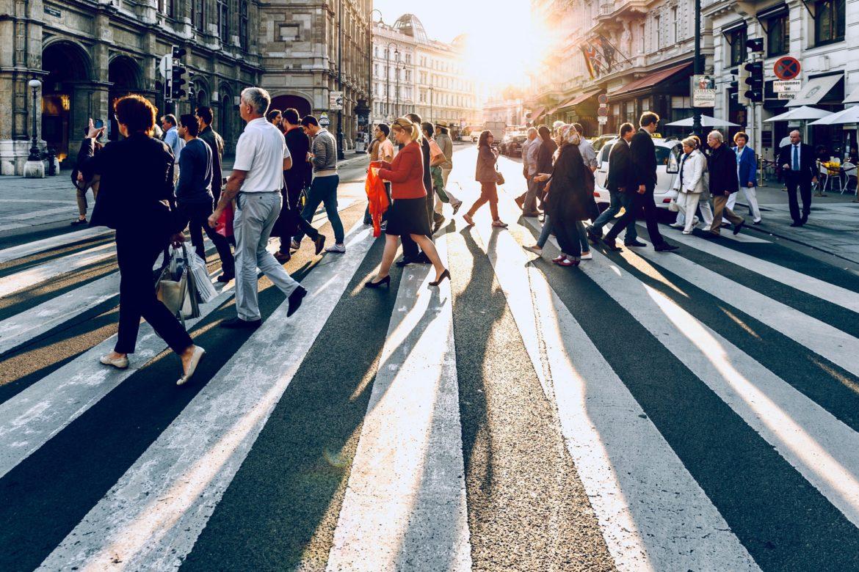 Menschen auf einem Zebrastreifen in der Sonne.