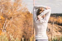 Frau stretch sich im Herbst in der Natur.