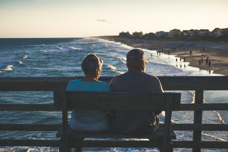 Älteres Paar auf einer Bank am Meer und Strand
