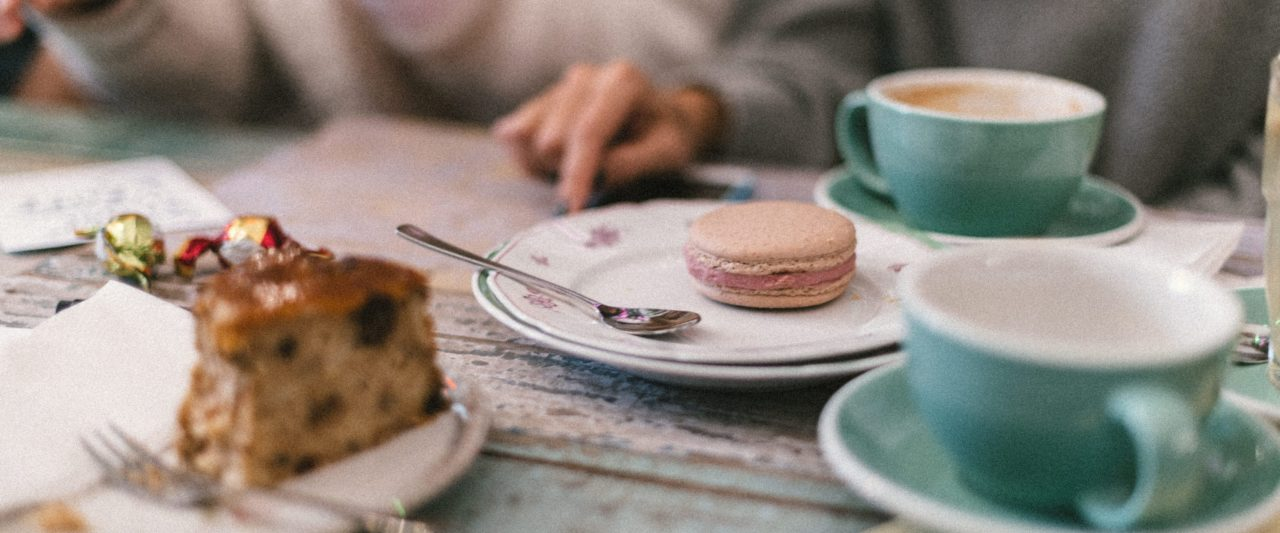 Grüne Tassen und Kuchen auf einem Holztisch