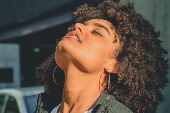 Dunkelhäutige Frau hält Gesicht in die Sonne mit geschlossen Augen - Gesunde Augen im Sommer