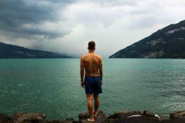 Mann in Badehose steht am See