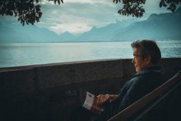Älterer Mann sitzt am See