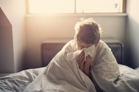Junge putzt Nase im Bett