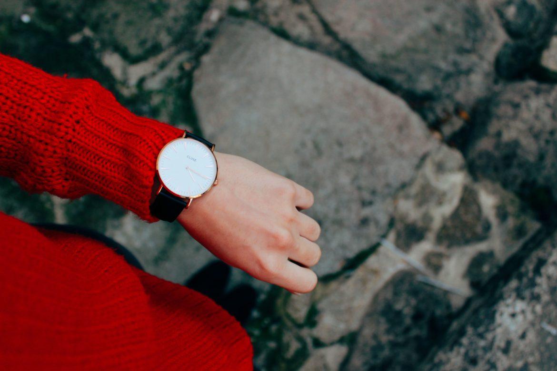 Frau mit rotem Strickpullover und Armbanduhr