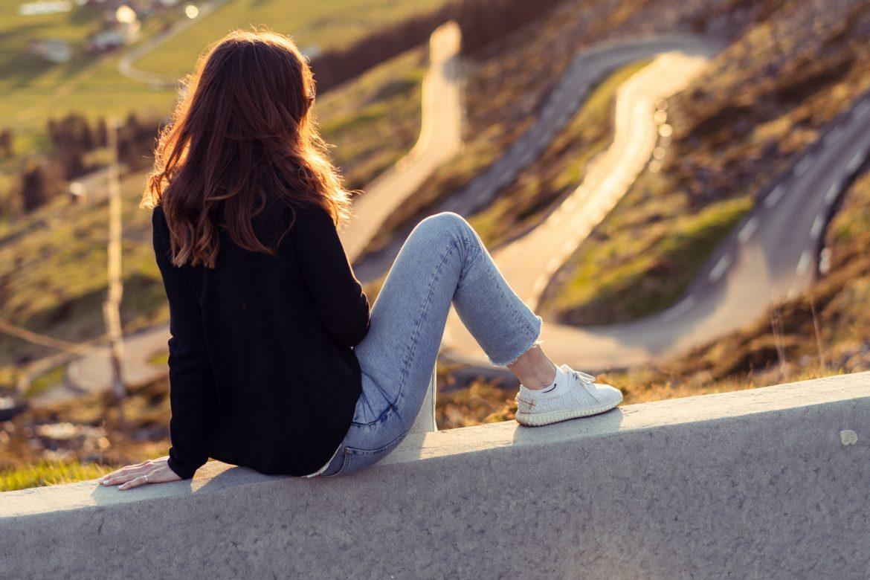 Junge Frau sitzt auf Mauer vor einer kurvigen Strasse