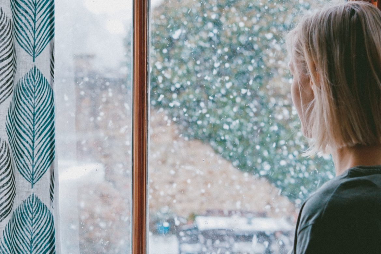 Frau am verschneiten Fenster