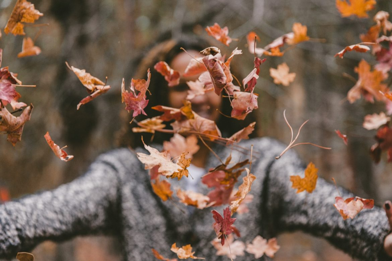 Frau im Herbst mit Laub