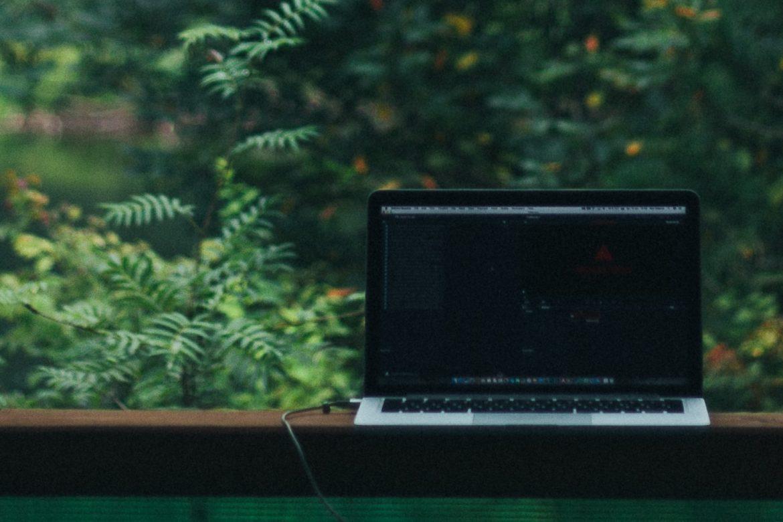 Laptop auf Fensterbank vor Wald