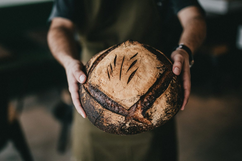 Mann hält dunkles Brot, Brotlaib
