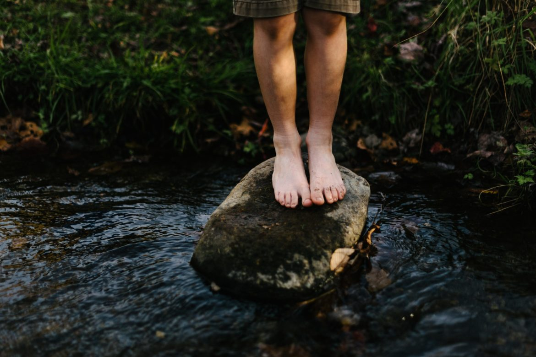 Beine auf Stein in Fluss