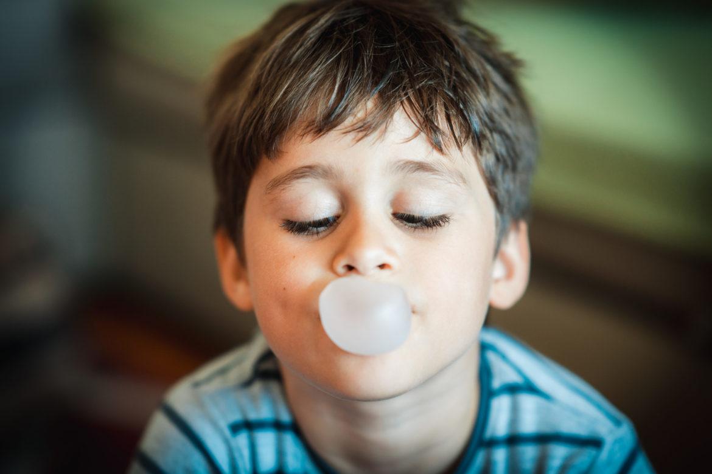 Junge der eine Kaugummi-Blase macht