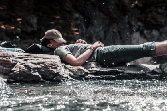 Mann liegt am Fluss