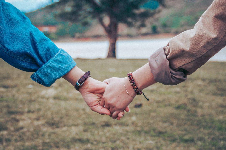 Paar, das Händchen hält mit Baum