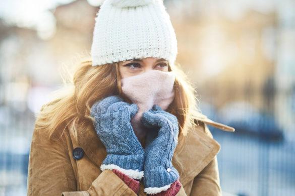 Frau im Winter putzt Nase