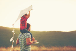 Kind mit Mann und Drachen in Natur
