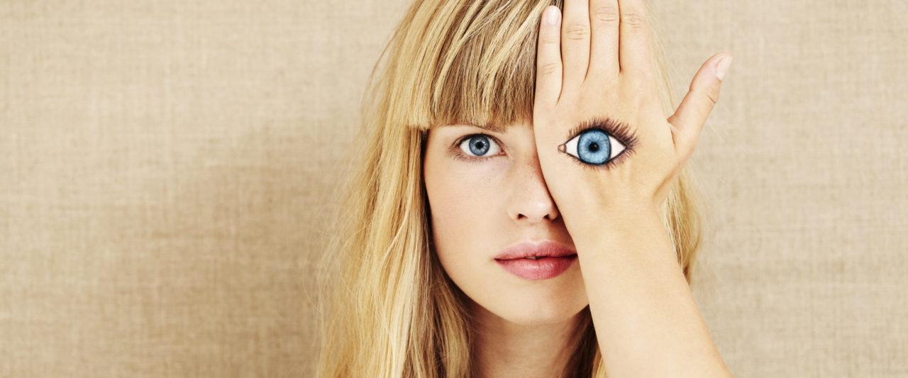 Blonde Frau mit gemaltem Auge auf der Hand