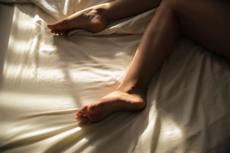 Beine von Frau in Bett