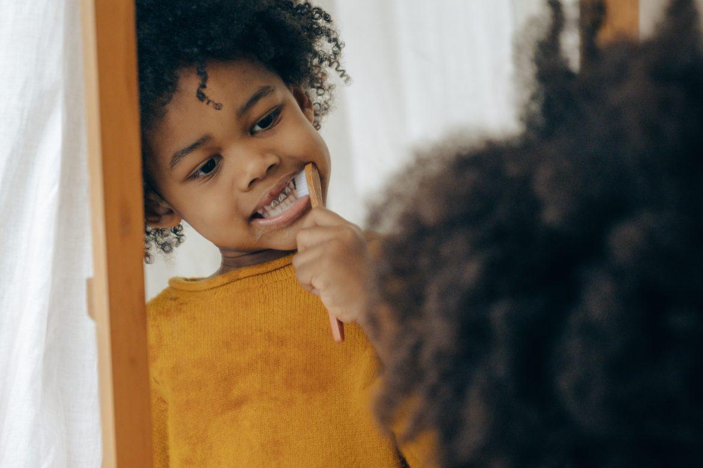 Kind putzt Zähne vor Spiegel