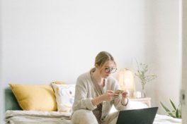 Frau auf Bett mit Laptop