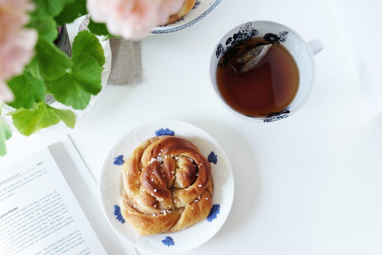 Tee und Gebäck auf Tisch mit Buch