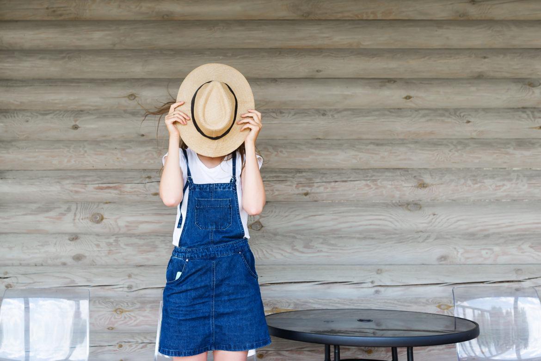 Frau mit Hut vor Gesicht